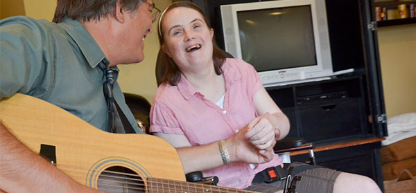 Pastor Playing Guitar With Church Member